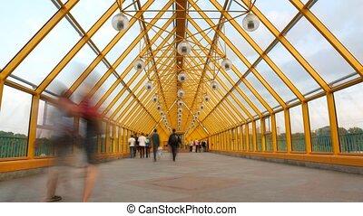 People go on the foot bridge, day.