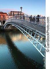People going on Ha'penny Bridge, Liffey River in Dublin, Ireland