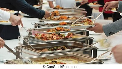 People group catering buffet food indoor in luxury restaurant with meat colorful fruits and vegetables. Close up. Banquet, lunch, bad nutrition, gluttony concept