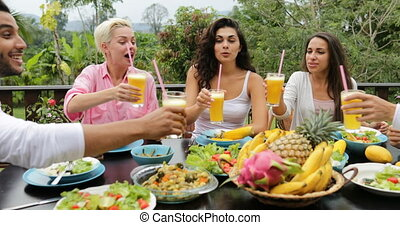 People Group Clink Juice Glasses Eating Healthy Vegetarian Food, Friends Communication Sitting At Table On Tropical Terrace
