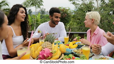 People Group Eating Healthy Vegetarian Food Talking, Happy Friends Clink Juice Glasses Sitting At Table On Tropical Terrace