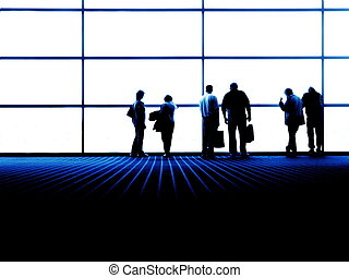 group of people looking out large city window