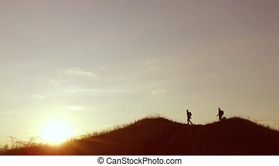 people group of tourists travel walking on top of a sunset silhouette mountain. slow video tourists people group go nature