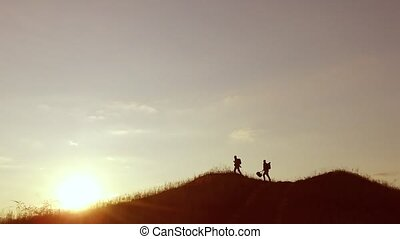 people group of tourists walking on top of a sunset silhouette mountain. slow video tourists people group travel go nature