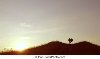 people group of tourists walking on top of travel a sunset silhouette mountain. slow video tourists people group go nature