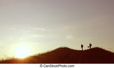 people group of tourists walking on top of a sunset silhouette mountain. slow video tourists people group go travel nature
