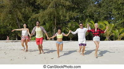 People Group Running On Beach Holding Hands, Mix Race Men...