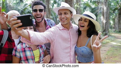 People Group Taking Selfie Photo On Cell Smart Phone On Hike, Men And Woman Trekking In Tropical Palm Tree Forest