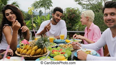 People Group Talk Eating Healthy Vegetarian Food, Friends Communication Sitting At Table On Tropical Terrace Pov Slow Motion 60