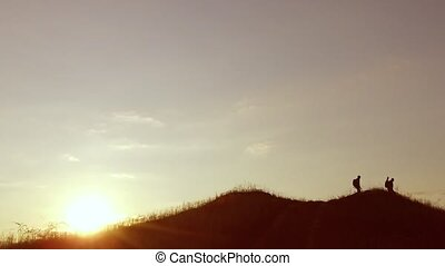 people group travel of tourists walking on top of a sunset silhouette mountain. slow video tourists people group go nature