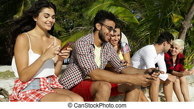 People Group Using Cell Smart Phones Communication Sitting Outdoors Under Palm Trees, Happy Smiling Man Woman Friends Chatting Online Talking
