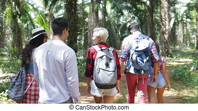 People Group With Backpacks Trekking On Forest Path, Young...