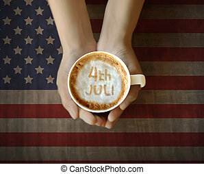 People hand holding cup of coffe with 4th of July message