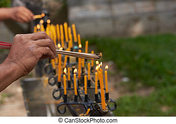 People hands burning incense from candles