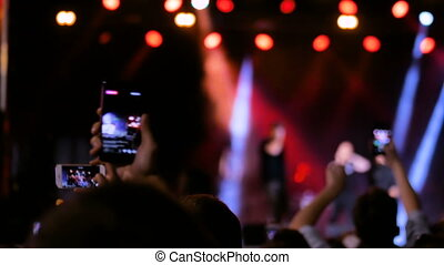People hands silhouette recording video of live music concert with smartphone