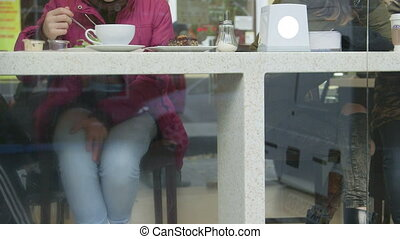 People have lunch at table by window in cafe on city street