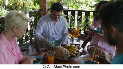 People Having Breakfast Sit At Table Talking On Balcony, Man...