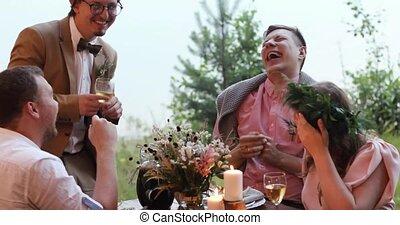 People having dinner and tells a joke in garden