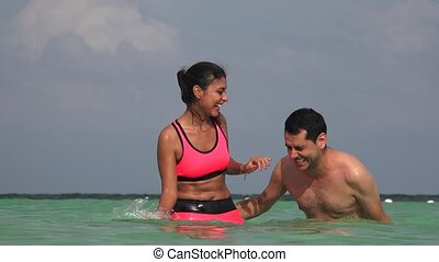 People Having Fun Swimming In Ocean On Vacation