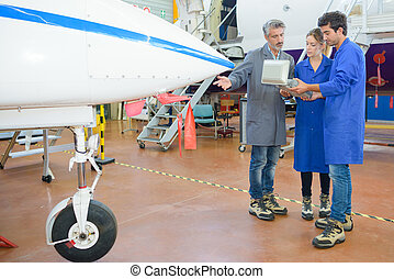 People having tour of aircraft hangar