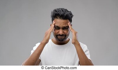 unhappy indian man suffering from headache - people, health...