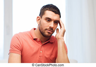 unhappy man suffering from headache at home