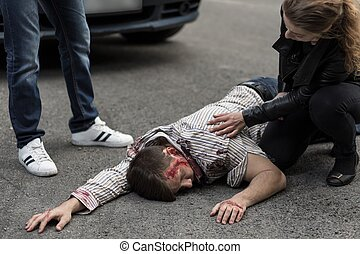 People helping injured man - Woman checking if man hit by a...