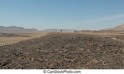 People hike at the bottom of the Ramon crater - HaMinsara...