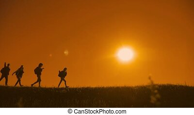 people hikers group and the dog silhouette of sunlight of...
