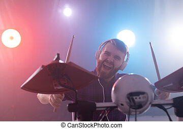 People, hobbies and music concept - close up portrait of a man with headphones playing electronic drums on the stage, having fun