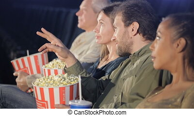 People hold buckets with popcorn in their hands at the movie theater