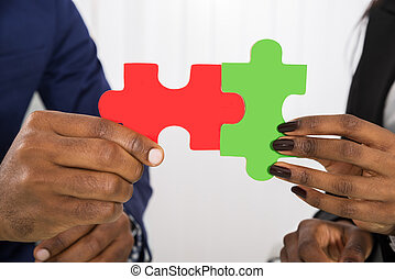People Holding Business Puzzle Pieces