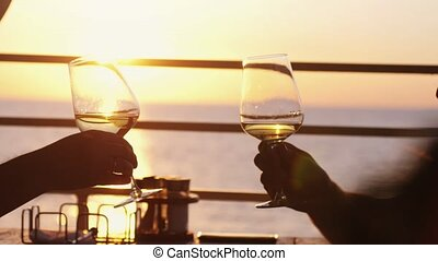 People holding glass of wine, making a toast over sunset....