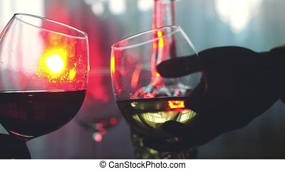 People holding glasses of wine making a toast in slow motion on the holiday table with lights bokeh on the background.