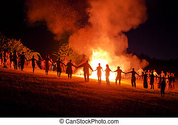 People holding hands and dancing in a circle around a fire at night