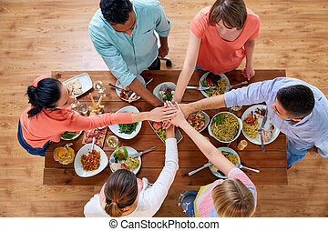people holding hands together over table with food