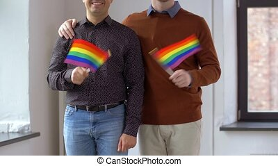 male couple with gay pride rainbow flags at home - people,...