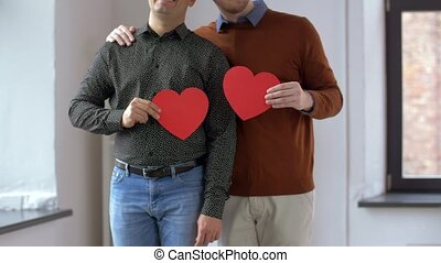 male gay couple with red heart shapes at home - people,...
