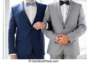 close up of happy male gay couple holding hands - people, ...