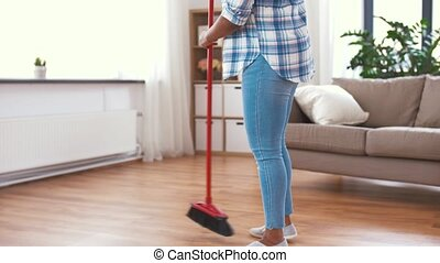 woman with sweeping broom brush cleaning floor - people,...