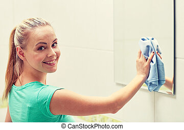 happy woman cleaning mirror with rag - people, housework and...