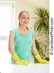 happy woman cleaning table at home kitchen
