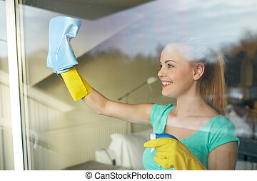 happy woman in gloves cleaning window with rag - people, ...