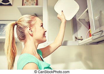 happy woman putting plate to kitchen cabinet - people,...