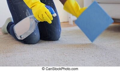 woman in gloves cleaning carpet or rug with rag