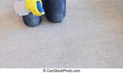 people, housework and housekeeping concept - woman in gloves cleaning carpet or rug with rag