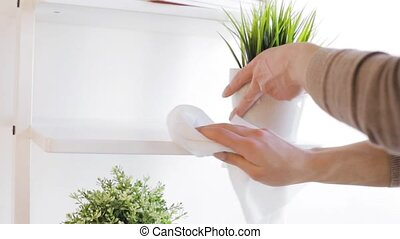 people, housework and housekeeping concept - woman with duster cleaning shelf from dust at home