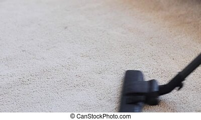 woman with vacuum cleaner cleaning carpet at home