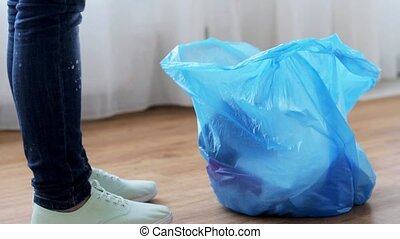 woman tying bag with garbage at home - people, housework,...