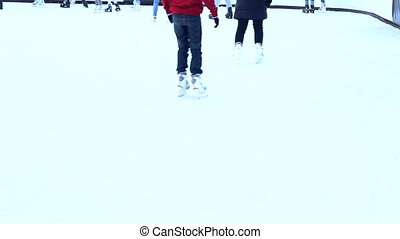 People Ice Skating in an outdoor rink